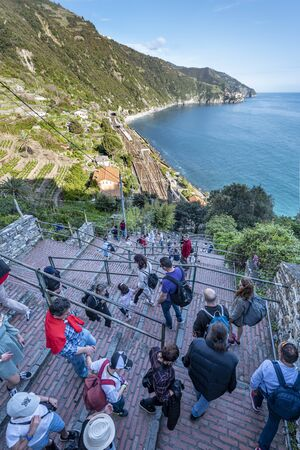 Corniglia, Italy -May 1, 2019 People tourists move own to the Corniglia village railway station via Lardarina staircase. Cinque Terre coastal area in Manarola village direction is at background.