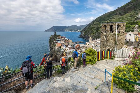 Vernazza, Italy-May 2, 2019 People tourists ingoing the view at Vernazza village and Cinque Terre coastal area from the Trial Sentiero Azzuro. Liguria, Italy. 報道画像