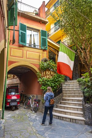 Monterosso, Italy - May 2, 2019 Woman tourist enjoying the passage in ancient village Monterosso in Cinque Terre coastal area. Liguria region in Italy.