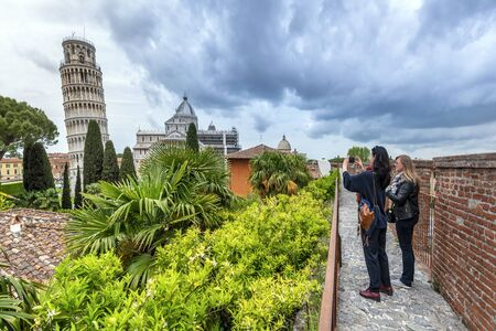 Pisa, Italy - May 3, 2019 Women tourists observing Pisa Tower from the city wall a the Gate San Ranierino.