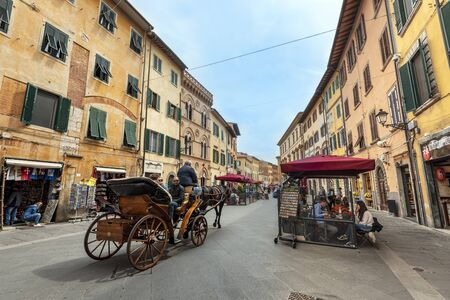 Pisa, Italy -May 3, 2019 The cart with people tourists moving through the old street of historical Pisa town. The souvenir shops and the restaurants occupy the sidewalks. 報道画像