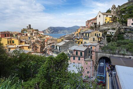 Vernazza, Italy ? ?? May 2, 2019 View at Vernazza village from the Railway sation with the train arrived and passengers tourists moving to the exit. Castello Doria is at left. Cinque Terre, Liguria, Italy.