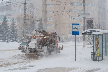 sleet: Snow-removal machine spreads sand and salt reagent on the carriageway. Snowfall in Cheboksary, Republic. Chuvashia, Russia.
