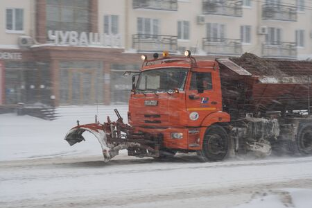 carriageway: Snow-removal machine spreads sand and salt reagent on the carriageway. Snowfall in Cheboksary, Republic. Chuvashia, Russia.