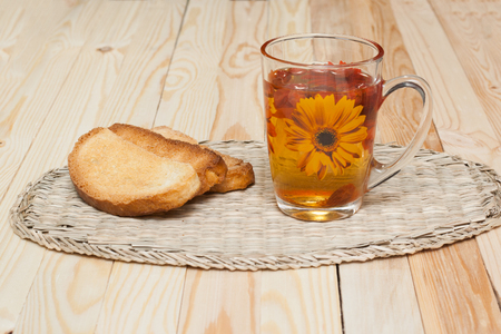 melba: Three biscuit to lie on a wicker napkin with a cup of rosehip compote. Foto de archivo