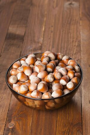 The crude hazelnut in translucent plate on the table with a wooden background. Vertical shot Healthy eating.