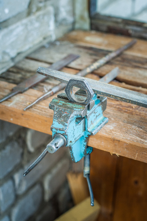 workpiece: Old workshop in the house. Machining a workpiece clamped in a vise. Old tools on a wooden table.