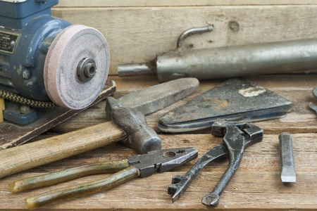 winepress: Set of old hand tools lying on a wooden bench. In the background of the winepress, with an electric motor and an old pipe. The old shop. Stock Photo