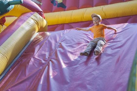 아이들은 놀고 공기와 함께 팽창 된 트램폴린을 타십시오. 도시 Cheboksary, 추바시 공화국, 러시아. 2011 년 3 월 18 일
