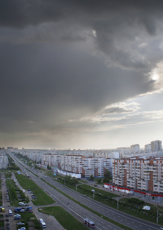 apartment tower old town: Urban landscape with a view of the avenue tratorostroiteley a storm cloud. Vertical frame. City Cheboksary, Chuvash Republic, Russia. Travel Russia. 05042016
