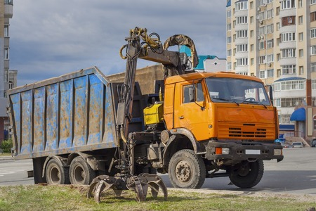 scrap iron: Old truck for transportation and loading of scrap in the city moved the tongs to grip scrap iron.