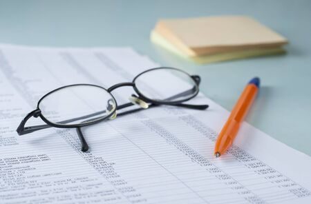 Workplace accountant. Documents, pen, glasses, paper for notes.