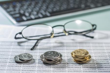 remuneraciÓn: Lugar de trabajo con monedas, documentos, teclado y vasos.
