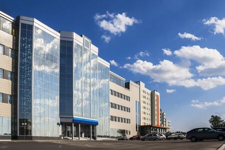 weather front: A large, modern office building and parking in front of the building. Clear weather with blue sky. Editorial
