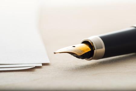 木製のテーブルに紙のシートで万年筆。