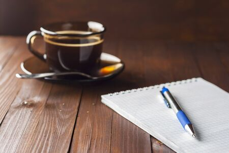 poems: Notebook with pen lie wooden table, and next to a cup of coffee.