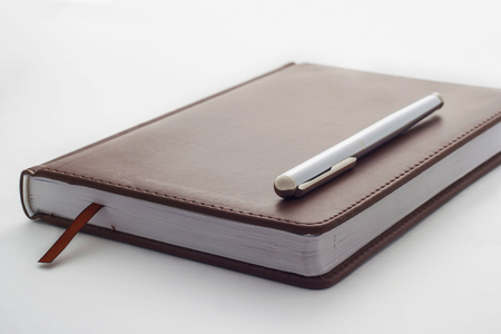 knowledgeable: metal handle lying on a leather-bound brown diary which belongs to businessman. Bookmark between the pages of the diary.