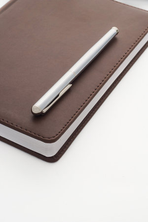 belongs: metal handle lying on a leather-bound brown diary which belongs to businessman. Veritkalny frame.