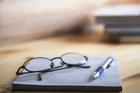 Notepad in the box with a pen and glasses on a wooden table in the background of a stack of books. Stock Photo