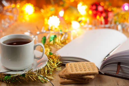 New entries. To-do list to the new year. List of shopping before the New Year. Notebook, cup of tea with cookies, Christmas toys lying on an old wooden table.