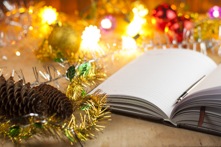 New entries. To-do list to the new year. List of shopping before the New Year. Notebook with pen, cones, Christmas balls lie on the old wooden table. Stock Photo