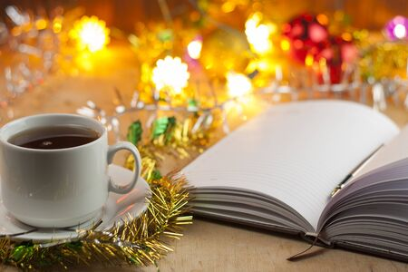 New entries. To-do list to the new year. List of shopping before the New Year. Notebook, cup of tea, Christmas toys with garlands lie on an old wooden table.