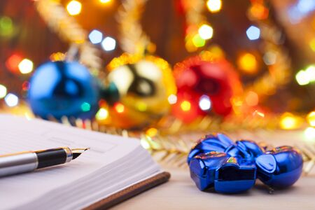 New entries. To-do list to the new year. List of shopping before the New Year. Christmas toys with garlands lie on an old wooden table.