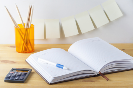 notepaper: Notepad with pen container with pencils, calculator are on a wooden table. White background. On the wall near the table glued paper for notes.
