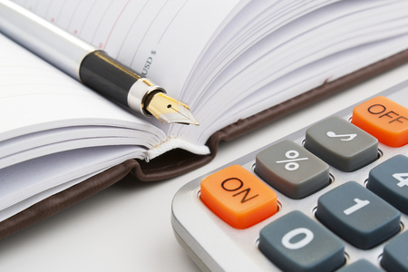ペンのビジネス ノート ブック。ハンドルはノートで。会計コスト。利益の計算。ビジネス計算。