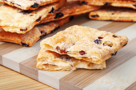 subtlety: Puff cookies with raisins on a cutting board made of bamboo stripes.