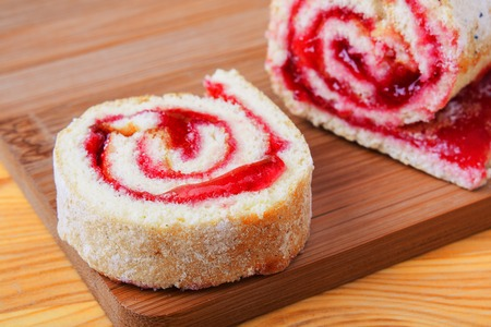 subtlety: Sweet roll with jam on a cutting board.