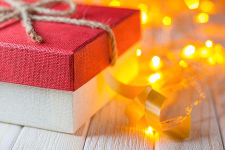 leds: caja de regalo sobre un fondo de madera con luces de guirnaldas de Navidad. Foto de archivo