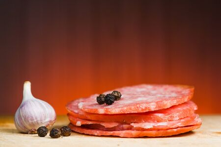 Thinly sliced pieces of salami on a cutting board. Wooden background.