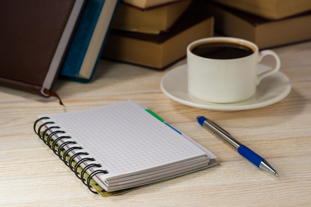 Notebook with pen on a wooden table in front of the window. A cup of hot coffee on the table. A stack of books. Stock Photo