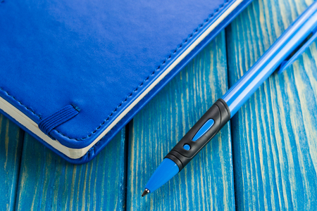 Stationery, notebook and pen on a blue wooden background.
