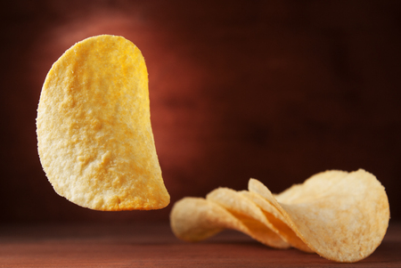 ranch background: Crispy potato chips on a wooden background. Chips in the air. Stock Photo