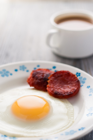 Breakfast on the table. Fried eggs with fried sausages salami and dill. Stock Photo