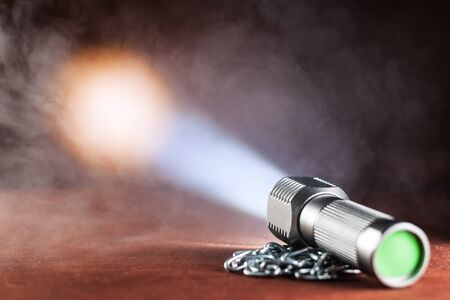 LED flashlight on a wooden table in the smoke. mini Stock Photo
