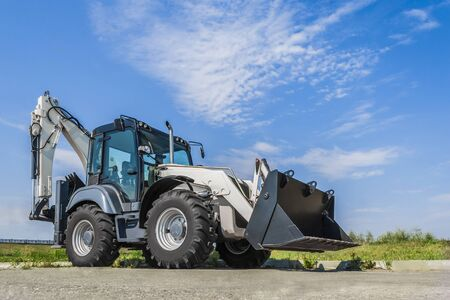 The new tractor is on the road in the city, a clear day with blue sky. Stock Photo