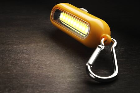 tourist flashlight key chain with carabiners on a wooden background.