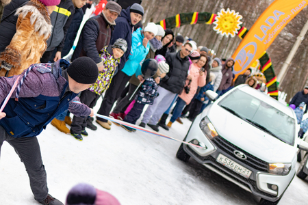 A man participates in the competition for the holiday Maslenitsa and drags a lightweight LADA car on a rope. City of Cheboksary, Russia, 03102019.