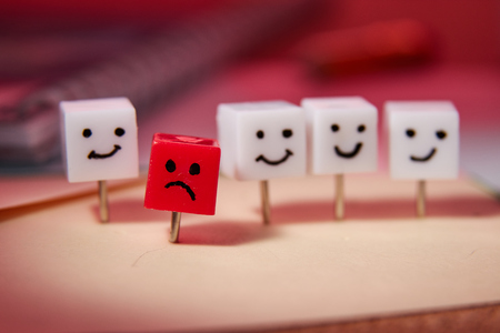 The concept of sadness, loneliness, disappointment. Shaped characters from office pins. Red background.