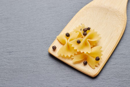 Pasta butterfly with pepper on a wooden spatula. Stock Photo