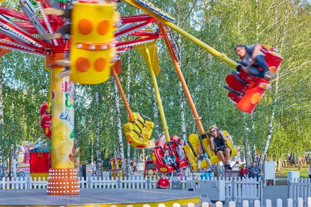 People ride the chain carousel in an amusement park. Cheboksary, Russia, 05112019