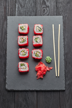 sushi rolls with red chopsticks and sauce on a slate table Stock Photo