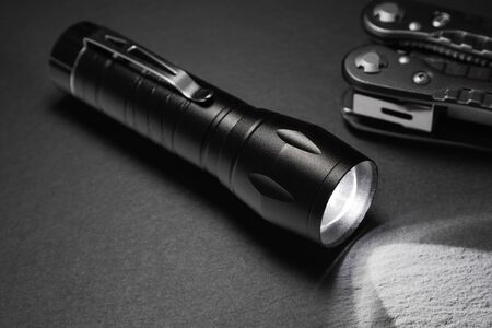 black flashlight on the stone surface. Tools for work, search and tourism .. Stock Photo