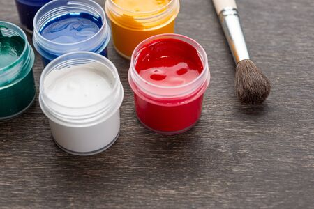 Looking down on three open paint cans of coloured paint stood on a shabby style wood floor