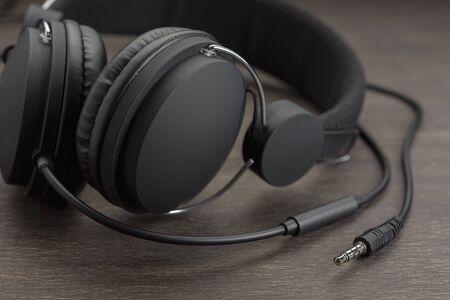 Dark headphones on a wooden background.
