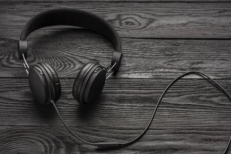 The headphones are dark in color against a wooden wall..