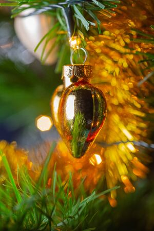Glossy Christmas toy in the shape of a heart hanging on a Christmas tree..